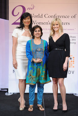 Mallika Dutt of Breakthrough receives the Avon Global Award for Excellence in Communications from Honorary Chairman of the Avon Foundation for Women Reese Witherspoon and Avon Chairman & CEO Andrea Jung.