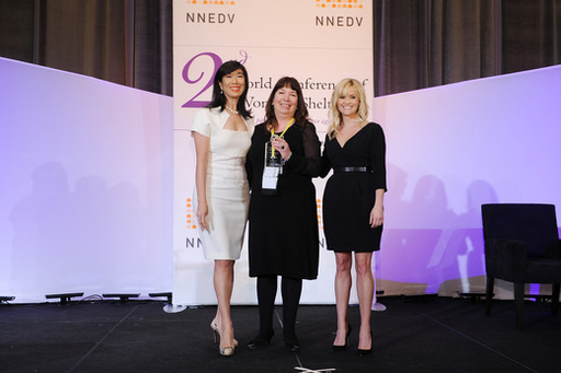 Nicola Harwin CBE of Women's Aid receives the Avon Storytelling Award from Honorary Chairman of the Avon Foundation for Women Reese Witherspoon and Avon Chairman & CEO Andrea Jung.