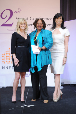 Mary V. Balikungeri of Rwanda Women Network receives the Avon Break the Silence Award from Honorary Chairman of the Avon Foundation for Women Reese Witherspoon and Avon Chairman & CEO Andrea Jung.