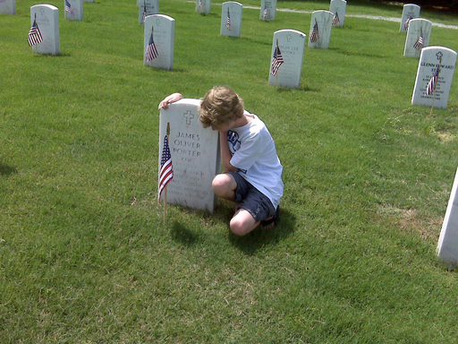 Hospice care not only honors Veterans at life's end but provides support to loved ones like Gavin Touchstone kneeling at his grandfather's grave in Arlington National Cemetery.