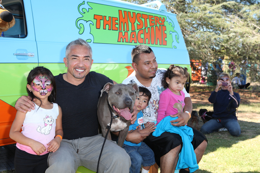Cesar Millan poses with a local family in front of the Scooby-Doo Mystery Machine.