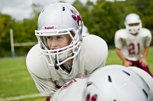 According to Riddell, a football helmet should fit snug and secure on the head and rest approximately one inch above the player's eyebrows.
