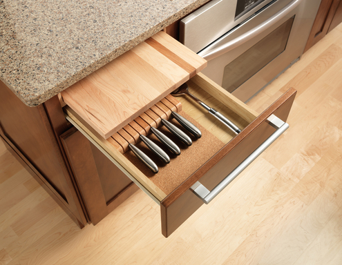 Small kitchens can seem larger with no clutter so hiding items that are often sitting out is smart. For example, the cutting board and knife storage are built into this drawer saving counter space.