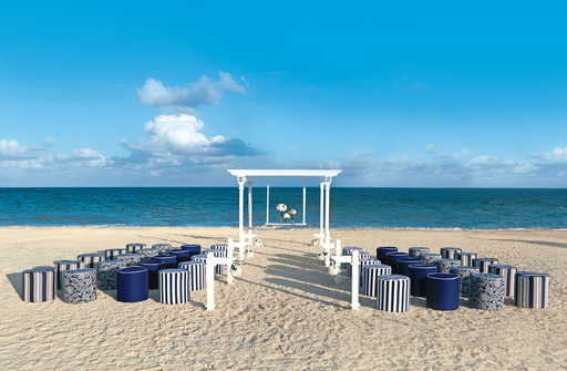 The Nautical wedding package displays crisp navy blue and white fabrics with bold floral arrangements along the aisle.