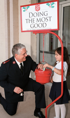A Salvation Army officer receives a red kettle donation from a young girl.
