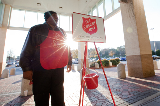 A Salvation Army bell ringer stands by a red kettle.