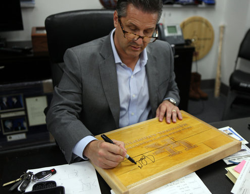 UK coach John Calipari signs a piece of the NCAA floor for an online charity auction presented by Northwestern Mutual to benefit the fight against childhood cancer.
