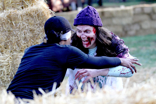 Run For Your Lives participant has face-off with zombie near hay maze obstacle.