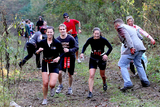 Runners dodge zombies as they trek through the woods, trying to keep their composure and their flags protected during the inaugural Run For Your Lives 5K in Darlington, Md.
