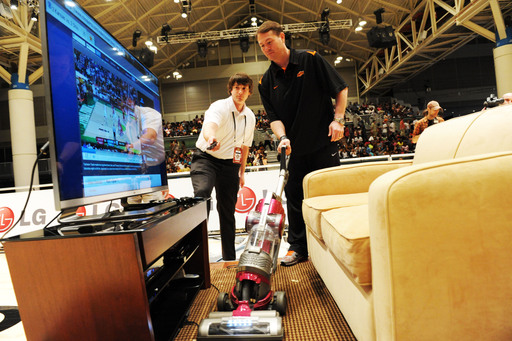 Oklahoma State University coach and former University of Kentucky all-star, Travis Ford cleans up the LG living room at the LG Home Court Challenge during the Final Four.