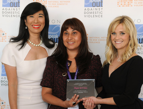 Andrea Jung and Reese Witherspoon present an Avon Global Believe Fund grant to Paola Perez, a gender and communities supervisor with Chile's Hogar de Cristo Foundation.
