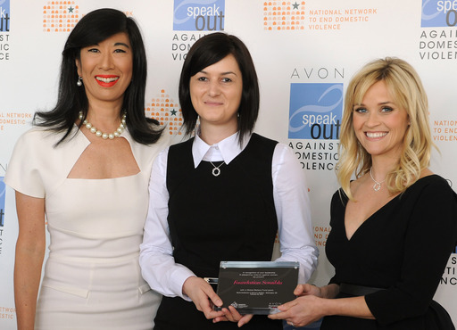 Andrea Jung and Reese Witherspoon present an Avon Global Believe Fund grant to Cristina Horia, executive director of Romania's Sensiblu Foundation.