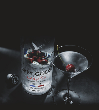 The Midnight Martinez - A dark and delicious mixture of GREY GOOSE Cherry Noir Flavored Vodka, NOILLY PRAT® Rouge and orange zest, this martini is presented with a plump, red cherry.