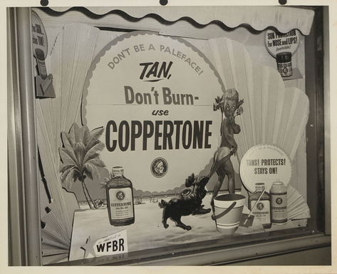 Little Miss Coppertone is featured in storefronts around the country, including this Florida window display in 1956.