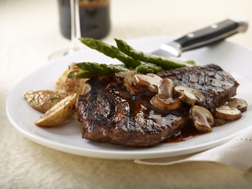 Piedmontese All-Natural Bone-In Strip Steak — with a red wine reduction, cremini mushrooms, grilled jumbo asparagus and fingerling potatoes