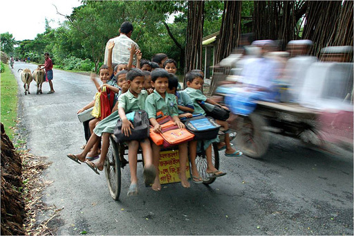 """School Bus,"" Kalloi Sen, India. A rickshaw puller drives kids to schoool using the van he bought through a microfinance loan."