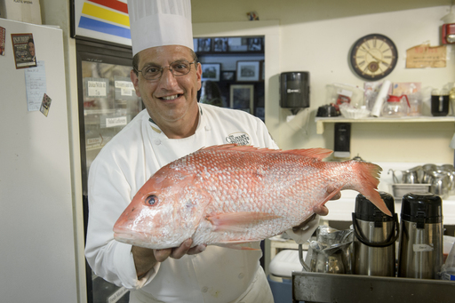Chef Phillip Crispo with The Culinary Institute of America holds a red snapper caught off the coast of Plaquemines Parish in Louisiana.