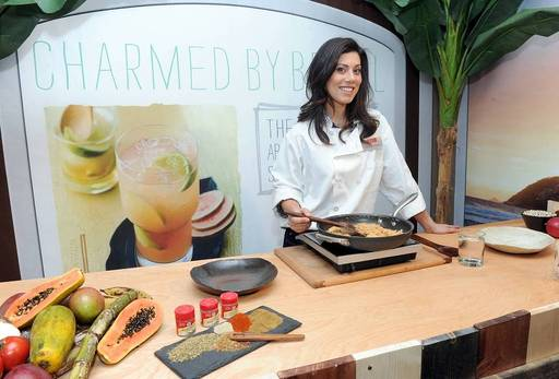 "Claire Robinson, host of Food Network's ""5 Ingredient Fix,"" demonstrates a Brazilian Farofa Topping, inspired by the McCormick Flavor Forecast 2014: 125th Anniversary Edition at the launch of McCormick's 125th anniversary, Dec. 3 in New York."