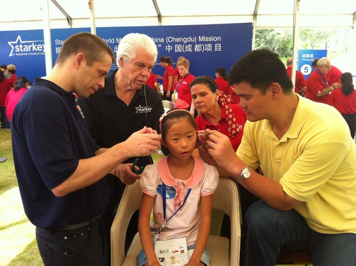 August 26, 2012, Starkey Hearing Foundation China (Chengdu) Mission – Child is fit by David Shoemaker, CEO, NBA China; Bill and Tani Austin, Co-Founders, Starkey; and NBA Legend Yao Ming.