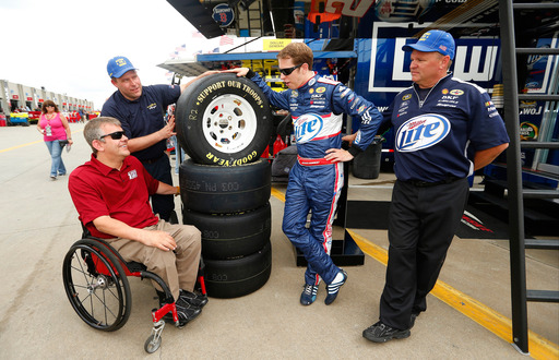 "Retired Navy pilot Mike Savicki (L), James Heath with Goodyear, Brad Keselowski and Jim Davis of the No. 2 car, with ""Support Our Troops"" tires at CMS for the ""Goodyear Gives Back"" Program, on May 23."
