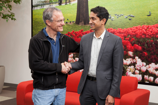 Stephen Kaufer and Premal Shah shake hands to celebrate new partnership and microlending program