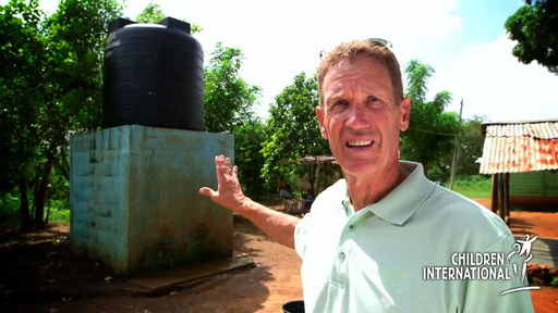 Dan Phelan points to the well and filtration system that changed lives in Manolito.