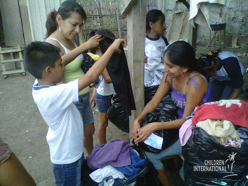Mothers and children select clothes from bags carefully sorted by size and gender by the youth leadership group.