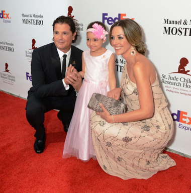 Carlos Vives and Claudia Helena Vasquez next to St. Jude Patient Izarah