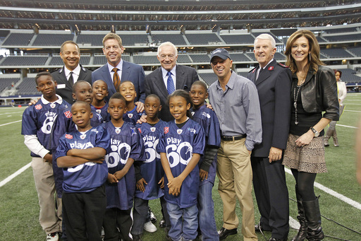 Troy Aikman, Jerry Jones, Charlotte Jones Anderson and officials from The Salvation Army join Kenny on-the-field at Cowboys Stadium to celebrate the Red Kettle Kickoff.