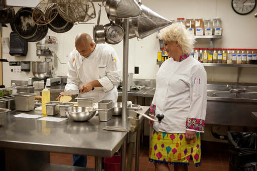 Host Anne Burrell encourages Chef David Sears as he slices potatoes for a dish