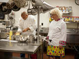 58436-host-anne-burrell-encourages-chef-david-sears-as-he-slices-potatoes-for-a-dish-sm