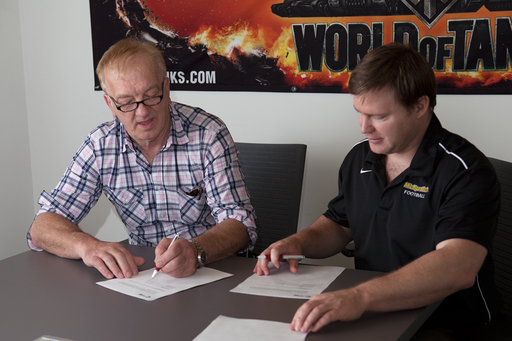 David Cundall and Jeremy Monroe, General Manager of Wargaming America, sign the agreement to fund David's expedition to Burma.