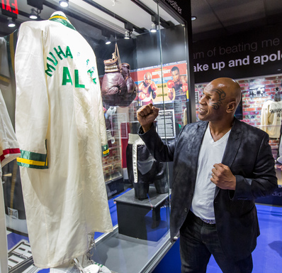 Mike Tyson views Muhammad Ali's robe in the boxing exhibit at the SCORE! grand opening at Luxor Las Vegas. The interactive sports attraction contains more than 300 prized pieces in eight galleries.