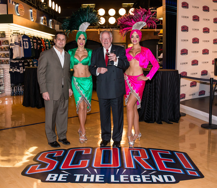 CEO of SCORE! At Luxor Las Vegas, James Beckmann and former Las Vegas Mayor Oscar Goodman celebrate the opening of the 10,000 square-foot interactive sports attraction with Las Vegas showgirls.