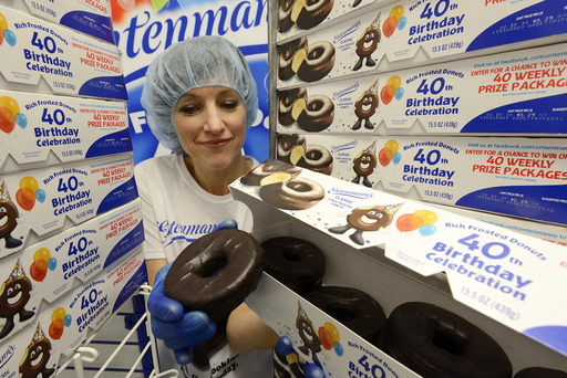 Kathleen Robbins, Entenmann's Master Baker, examines the 400,000,000th Rich Frosted Donut for quality control at Entenmann's Bakery in Carlisle, Pennsylvania on January 31, 2013, marking the 40th birthday of the Rich Frosted Donut.