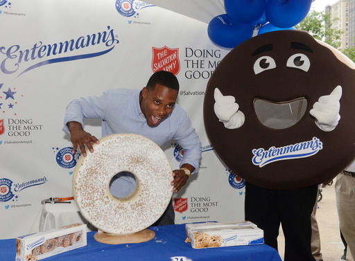 Super Bowl Champion, Victor Cruz, takes a bite out of a specially made Entenmann's Crumb Top Donut on National Donut Day at the Madison Square Park event with Entenmann's and The Salvation Army.