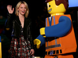 "Actress Elizabeth Banks gives a high-five to LEGOLAND California Resort's newest costume character Emmet from ""The LEGO Movie"" at the Park's tree lighting ceremony in Carlsbad, California."