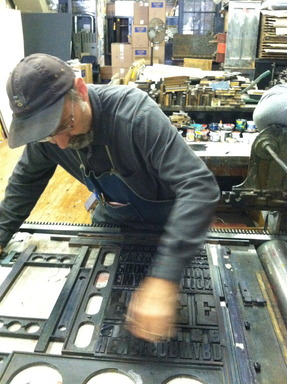 Hatch Show Print Manager, Jim Sherraden, applies ink with a brayer to the type of the Emancipation Proclamation Stamp in Nashville, TN.