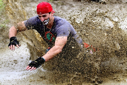 A brave Run For Your Lives participant plunges into muddy waters to escape a fast-approaching zombie horde.