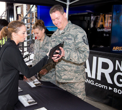 A visitor to the Air National Guard Mobile Experience speaks with a recruiter to learn more about how she can serve her country part time in the Air National Guard.
