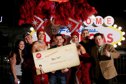 Hector Parra celebrates winning a $5,000 Las Vegas summer trip. He won by breaking open a giant pinata fashioned after the destination's ad campaign character Mr. Las Vegasdotcom.