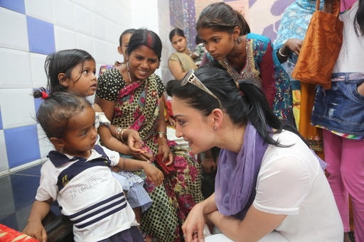 Actress and Rotary polio ambassador Archie Panjabi visits with young children at a health clinic in New Delhi, India.