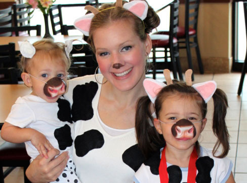 A mother and her daughters in homemade costumes for Cow Appreciation Day.