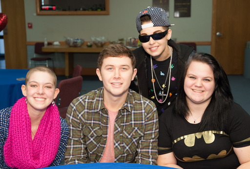 American Idol alum Scotty McCreery visits with St. Jude patients Hailey, Kelli and Maycel .