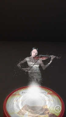 A violinist plays Bach's Innovations No. 14 as part of the Häagen-Dazs Concerto Timer mobile app. She appears on a user's device for two minutes when a carton of ice cream is aligned with the app.