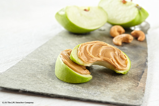 Jif® Cashew Butter spread on an apple.
