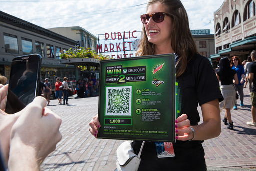 "A Mountain Dew® representative holds up an ""Every 2 Minutes"" QR code worth 1000 points for fans to scan at the Pike Place Market in Seattle, Wash. Over 100 QR codes were placed throughout the Washington Convention Center and local landmarks."