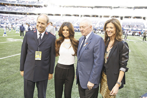 Selena Gomez joins Major Ron Busroe of The Salvation Army, Jerry Jones and Charlotte Jones Anderson of the Dallas Cowboys on the field after being announced as the Red Kettle Kick-off and Halftime performer of the Thanksgiving Day Cowboys game