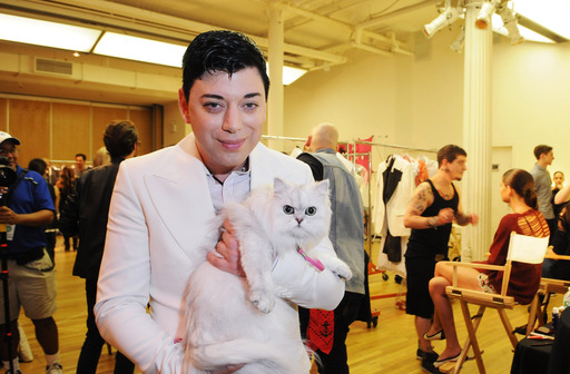 Designer Malan Breton appears backstage with the Fancy Feast cat before his STYLE360 show during New York Fashion Week. Breton's collection featured four looks inspired by the iconic Fancy Feast cat.