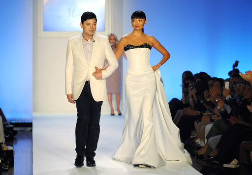 Malan Breton walks the runway with model Irina Pantaeva at his STYLE360 show. The gown, which featured a 17-foot-long train, was one of four looks in his collection inspired by the Fancy Feast cat.